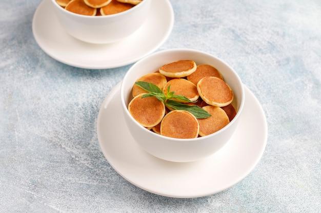 Trendy food - mini-pfannkuchen-müsli. haufen müsli-pfannkuchen mit beeren und nüssen.