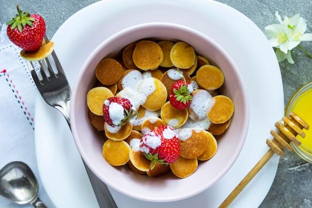 Trendy food - pfannkuchen müsli. haufen mini-müsli-pfannkuchen mit erdbeeren. draufsicht.