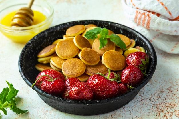 Trendy food - pfannkuchen müsli. haufen mini-müsli-pfannkuchen mit erdbeeren, honig und minze in gusseiserner pfanne