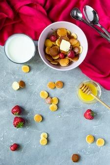 Trendy food - pfannkuchen müsli. haufen mini-müsli-pfannkuchen mit erdbeeren in gusseiserner pfanne. roter hintergrund und kopierraum