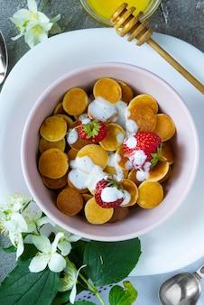 Trendy food - pfannkuchen müsli. haufen mini-müsli-pfannkuchen mit erdbeeren und joghurt in leichtem boul. draufsicht oder flache lage.