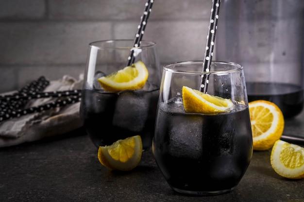 Trendy food summer erfrischungsgetränke detox und diät-konzept schwarze limonade mit kohleeis zitronensaft und zitrone