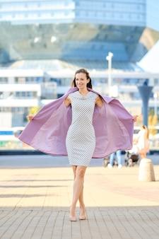 Trendy frau im gestreiften kleid wirft offenen lila mantel im freien