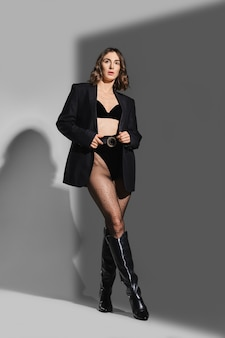 Trendy frau in höschen mit hoher taille, blazer und lederreitstiefeln posiert im studio