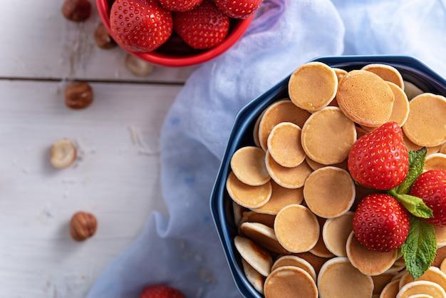 Trendy getreidepfannkuchen in der blauen schüssel mit erdbeeren und haselnüssen auf blauer gaze, draufsicht