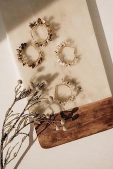 Trendy handgemachte ohrringe und blumenzweig auf marmorbrett auf weiß
