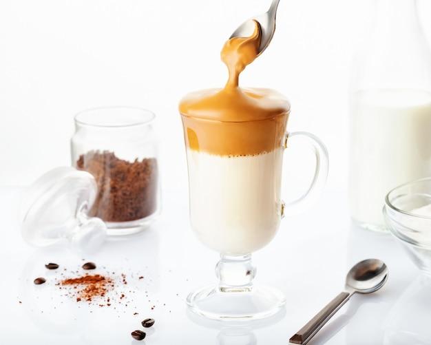 Trendy hausgemachter dalgona kaffee in glasschale mit zutaten, instantkaffee, milch und zucker isoliert. rezept beliebte koreanische getränk latte mit schaum instantkaffee.