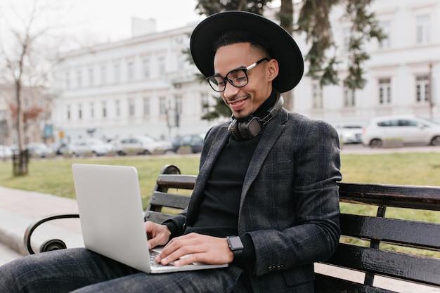 Trendy internationaler student, der mit laptop im park arbeitet. lächelnder afrikanischer mann, der draußen mit computer kühlt.