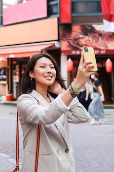 Trendy junge frau, die ein selfie nimmt