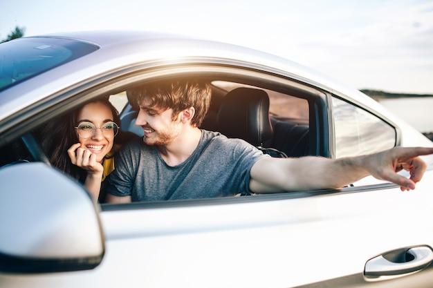 Trendy junge frauen und mann, die mit dem auto reisen. entspanntes glückliches paar im sommer-roadtrip-reiseurlaub.