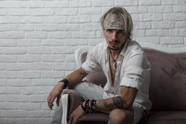 Trendy junger blonder mann in einem grauen kopftuch in einem weißen hemd in zerrissenen stilvollen jeans mit einem tattoo mit lederarmbändern ruht auf einem vintage-sofa