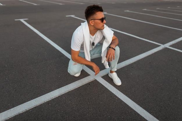 Trendy junger mann in stilvollen jeans in einem weißen vintage-t-shirt in modischer sonnenbrille mit einem sweatshirt sitzen auf einer straße mit weißen linien. urban modern guy entspannt sich auf der straße. herrenbekleidung.