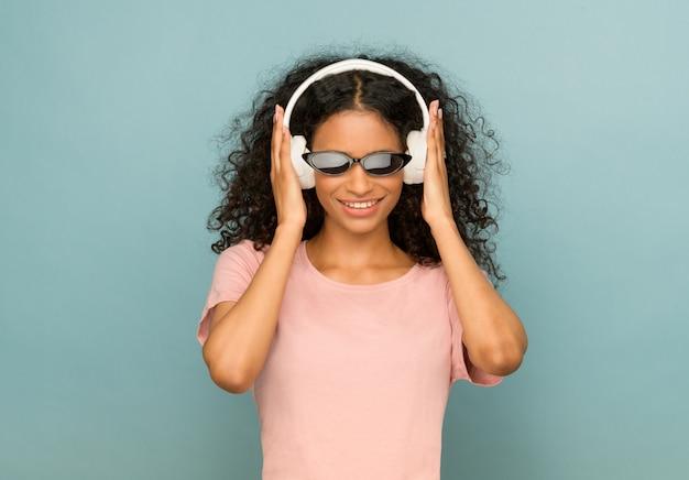 Trendy junges afroamerikanisches mädchen, das sonnenbrille und kopfhörer trägt