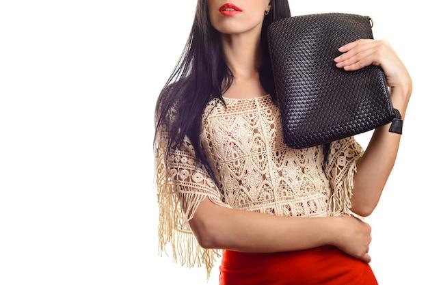 Trendy junges mädchen im roten rock, der schwarze lederhandtasche weiß hält