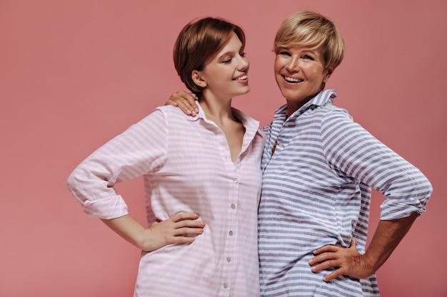 Trendy junges mädchen mit brünettem haar in den rosa gestreiften kleidern, die mit der alten blonden frau im blauen kleid auf lokalisiertem hintergrund lächeln und umarmen.