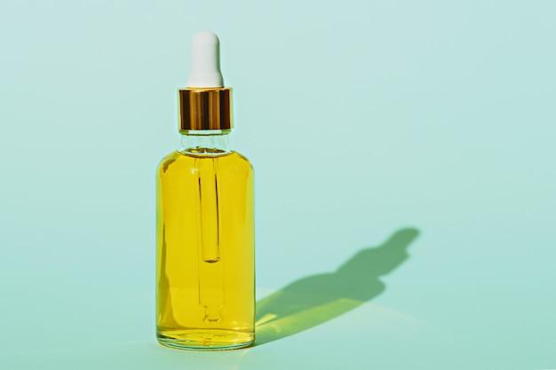 Trendy kosmetikflasche mit pipette und gelbem öl auf blauem hintergrund mit schatten mit kopienraum, tropfflaschenkonzept
