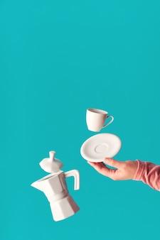 Trendy levitation fliegende kaffeebohnen, espressotasse mit untertasse, die auf zeigefinger der weiblichen hand balanciert. levitation der keramischen kaffeemaschine. trendy mintblaue kaffeewand, platz für ihren text.