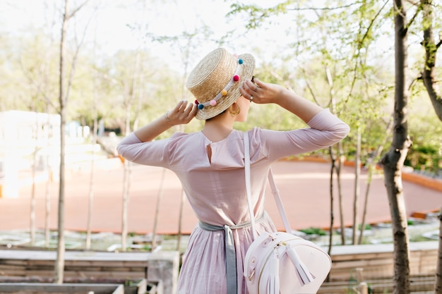 Trendy mädchen, das altmodisches lila kleid und strohhut trägt, die reizende ansicht während des spaziergangs genießen