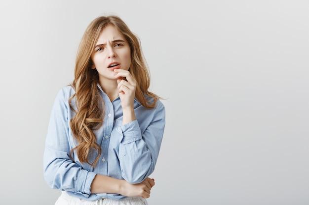 Trendy mädchen, das zweifel über neues kleid hat. ungläubig aussehende studentin in blauem hemd, lippe berühren und mit besorgtem ausdruck starren, über graue wand nachdenken