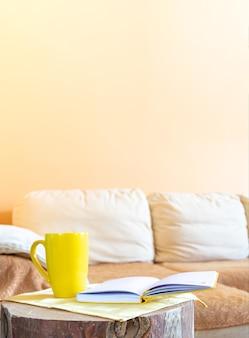 Trendy minimales wohnambiente zur entspannung: bequeme hellbeige große couch, kreativer holzstumpf als tisch mit gelber tasse und notizblock.