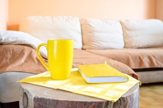 Trendy minimales zuhause wirklich gemütliches interieur zum entspannen: bequemes helles großes ecksofa, kreativer holzstumpf als tisch mit gelber tasse und notizblock aus der nähe. Premium Fotos