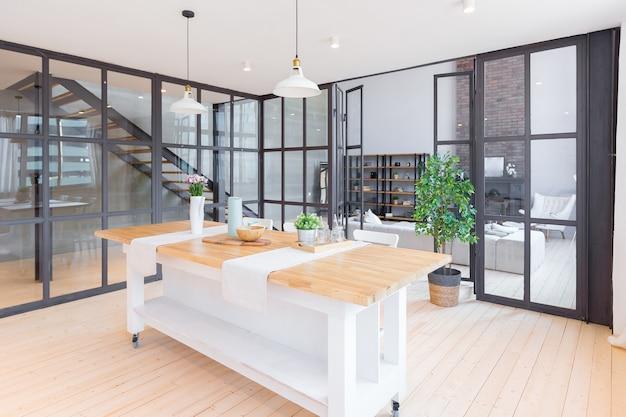 Trendy modernes design zweistöckige wohnung mit großen hohen fenstern. das stilvolle wohnzimmer und die küche in hellen farben werden durch eine glastrennwand ausgezogen. schlafzimmer im zweiten stock.