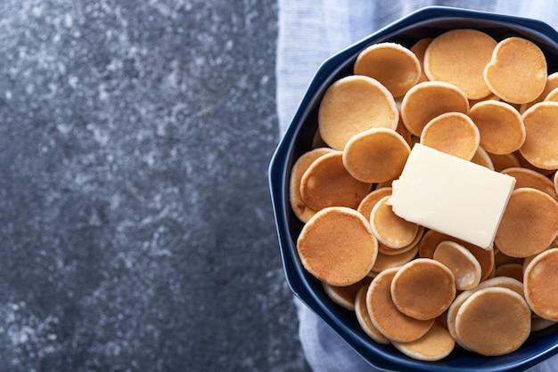 Trendy müsli pfannkuchen in der blauen schüssel mit butterbrot auf blauer gaze auf grau