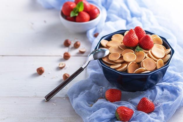 Trendy müsli pfannkuchen in der blauen schüssel mit erdbeeren und haselnüssen auf blauer gaze auf weißem holz