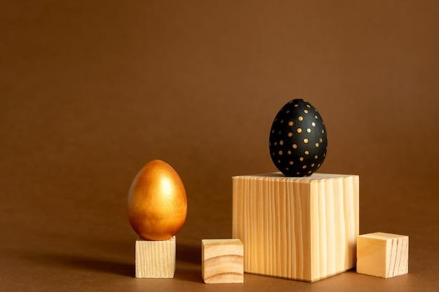 Trendy osterhintergrund. goldene und schwarz bemalte eier stehen auf holzwürfeln, podien auf braunem hintergrund.