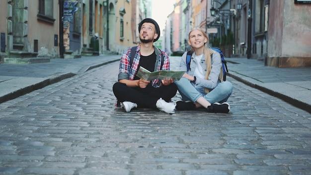 Trendy paar touristen, die karte verwenden, auf bürgersteig sitzen und historische umgebung bewundern