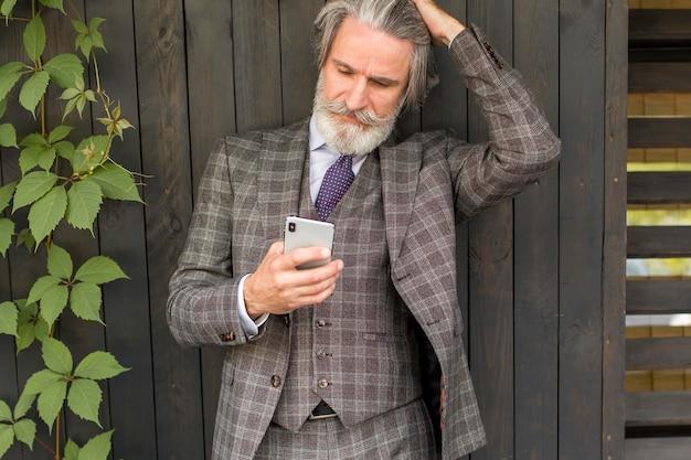 Trendy reifer mann mit bart, der telefon durchsucht
