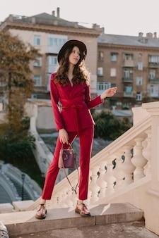 Trendy schöne stilvolle frau im lila anzug, der in der stadtstraße, frühlingssommer-herbstsaison-modetrend trägt hut trägt und geldbörse hält