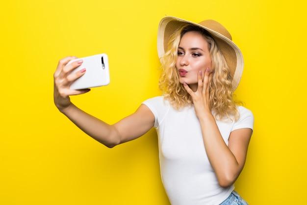 Trendy schönes kühles blondes mädchen, das einen strohhut trägt, der selfie mit handy gegen eine gelbe wand nimmt.