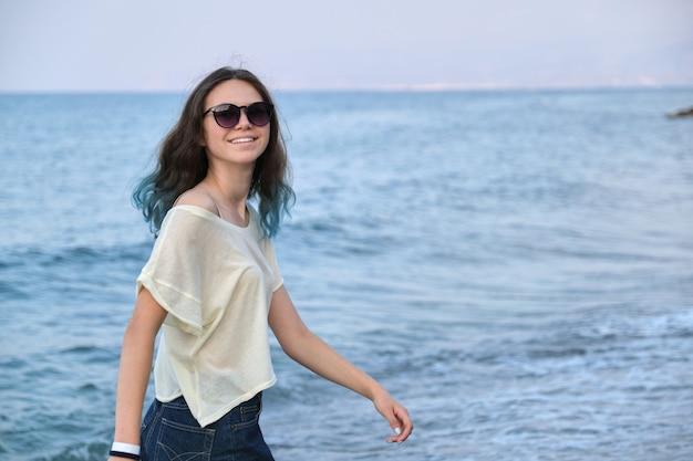 Trendy schönes teenager-mädchen mit langen blauen haaren in sonnenbrillen und shorts, die entlang des meeresstrandes gehen