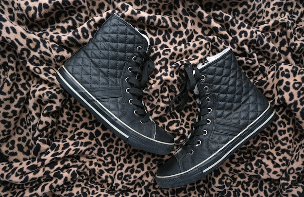 Trendy schwarze gesteppte lederturnschuhe auf tierdruckhintergrund. schwarz-goldener gepard-leopard entdeckt strukturierten stoff. modeschuhe schuhkonzept. flatlay.