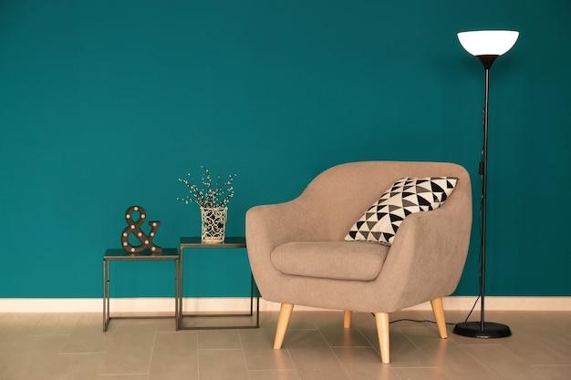 Trendy sessel mit lampe und tischen nahe schattierter fichtenwand
