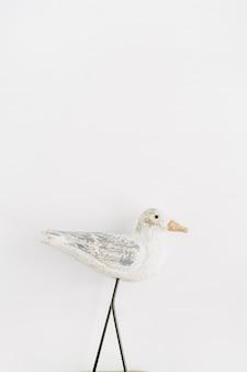 Trendy stilvoller innenfigurenholzvogel auf weißer oberfläche