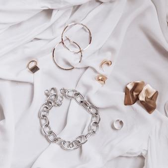 Trendy stilvolles schmuckset auf weißem stoff