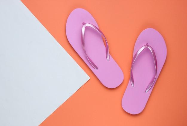 Trendy strand rosa flip flops auf korallenweißpapierhintergrund. speicherplatz kopieren. draufsicht
