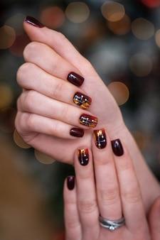 Trendy und schöne maniküre auf frauenhänden. nägel purpur oder burgunder in kombination mit goldglanz.