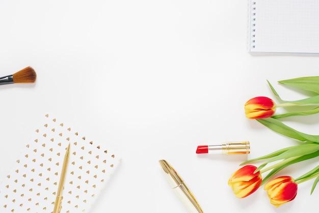 Trendy weiblicher heimarbeitsplatz. home-office-schreibtisch mit laptop, notebook, tulpe, stift, zubehör und kosmetik auf weißem hintergrund. valentine flat lay, draufsicht mit kopierraum