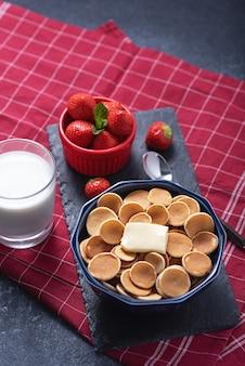 Trendy winzige müsli-pfannkuchen mit butterscheibe in blauer schüssel, erdbeeren, glas milch auf rot