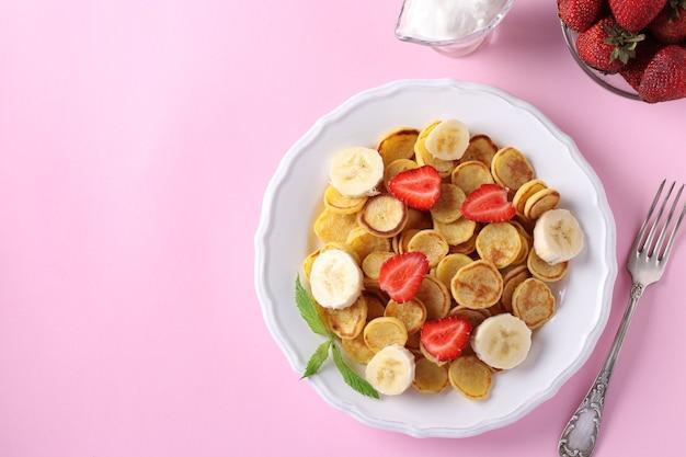 Trendy winzige pfannkuchen zum frühstück mit erdbeere, banane und saurer sahne in der weißen platte auf rosa hintergrund. sicht von oben. kopieren sie platz für text oder design