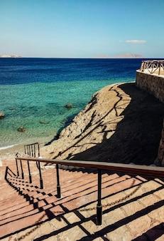 Treppe hinunter zum strand mit blauem meer. treppe zum meer