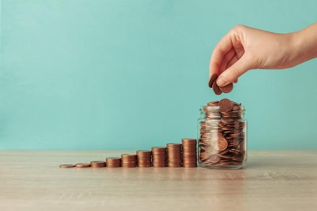 Treppe mit münzen, einem glas und einer hand