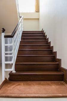 Treppenhaus nach maß mit holztreppe und weißen wänden.