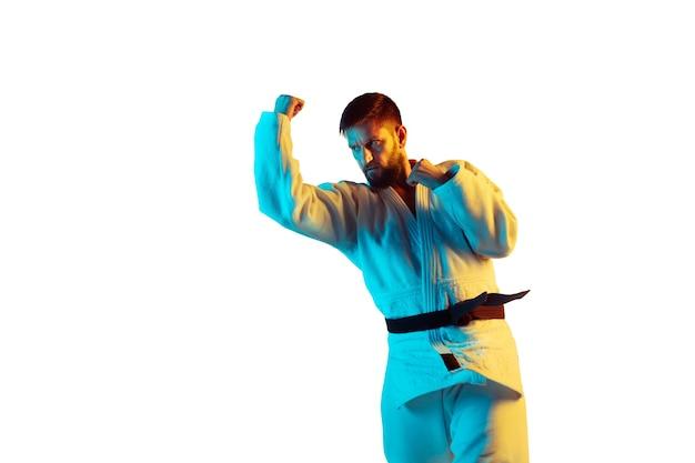 Trete. selbstbewusster trainer im kimono, der nahkampf übt