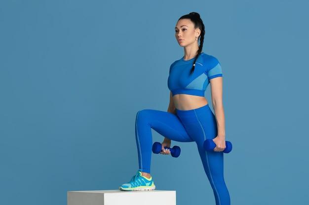 Treten. schöne junge sportlerin, die im studio übt, einfarbiges blaues porträt