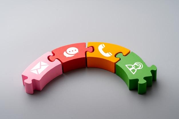 Treten sie mit uns ikone auf buntem puzzlespiel mit der hand in verbindung