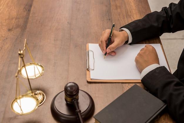 Tribunal attorney-rechtsanwalt, der mit dokumenten und hölzernem hammer auf tabelle im gerichtssaal arbeitet.
